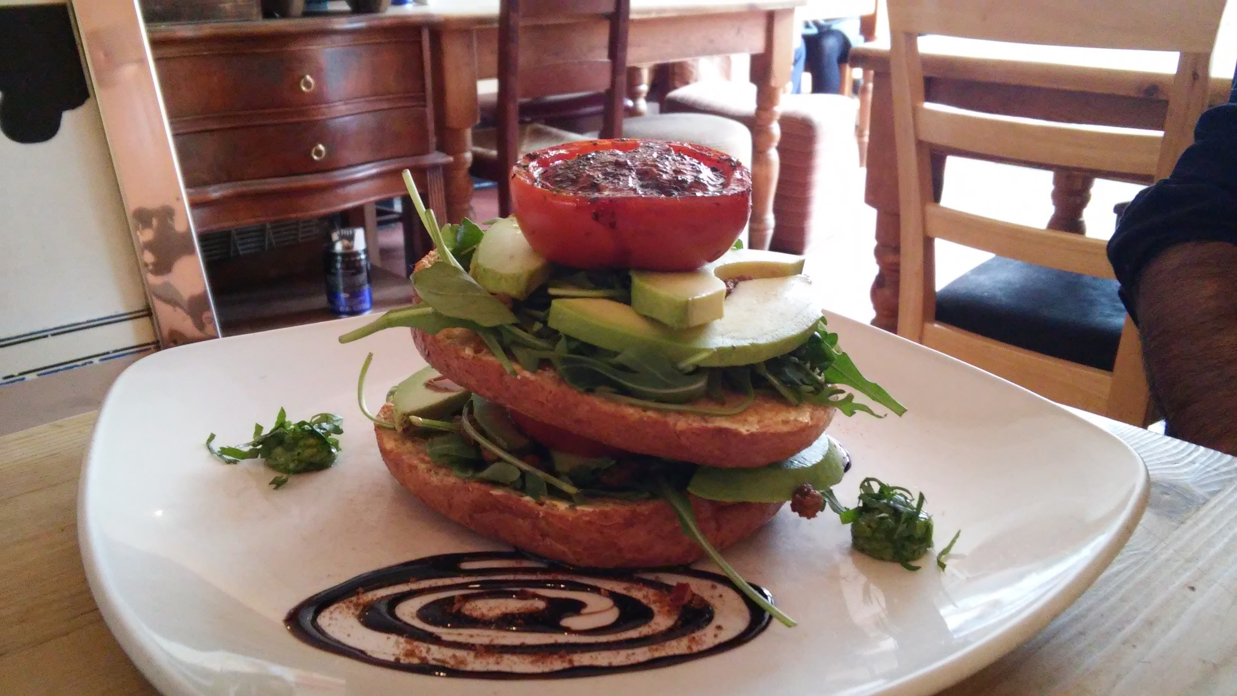 The griddle bagel with avocado, slow roast balsamic tomato, fresh rocket and cashew nut pesto topped with a balsamic reduction