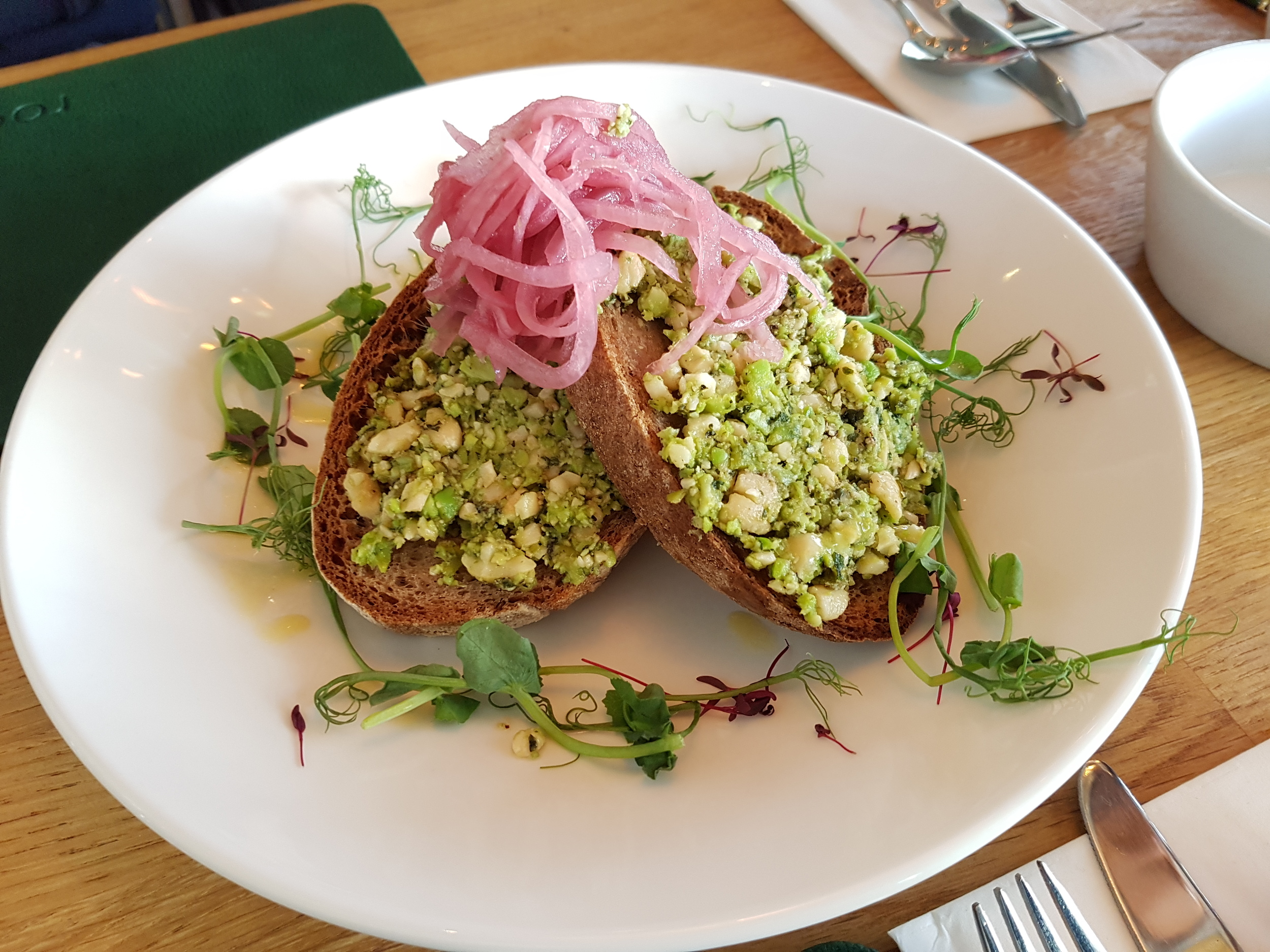 Fresh mint, broad bean & cashew pate on toasted sourdough, garnished with pickled red onion