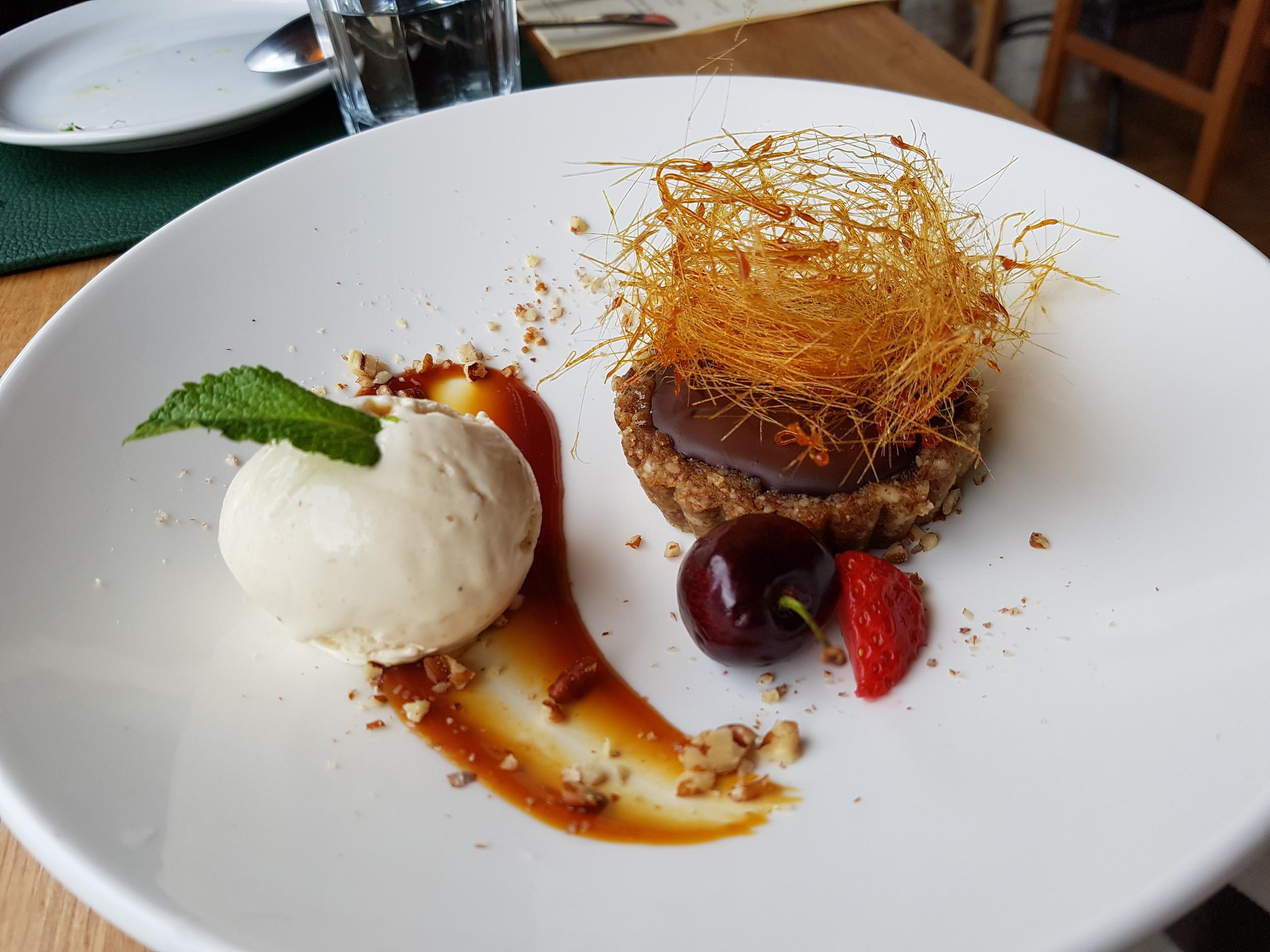 Chocolate ganache tart with a mixed nut and date base, salted caramel, spun sugar and vanilla ice cream