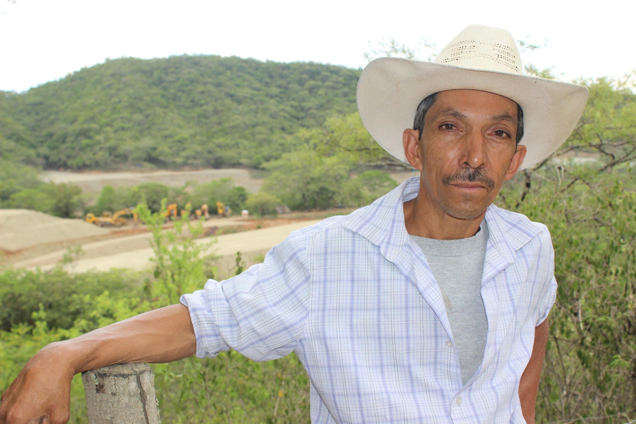 Eusebio, miembro activo de la resistencia pacífica de La Puya y la maquinaria de construcción en la mina. Eusebio, a long-standing member of the peaceful resistance, overlooking the construction machinery at the mine.