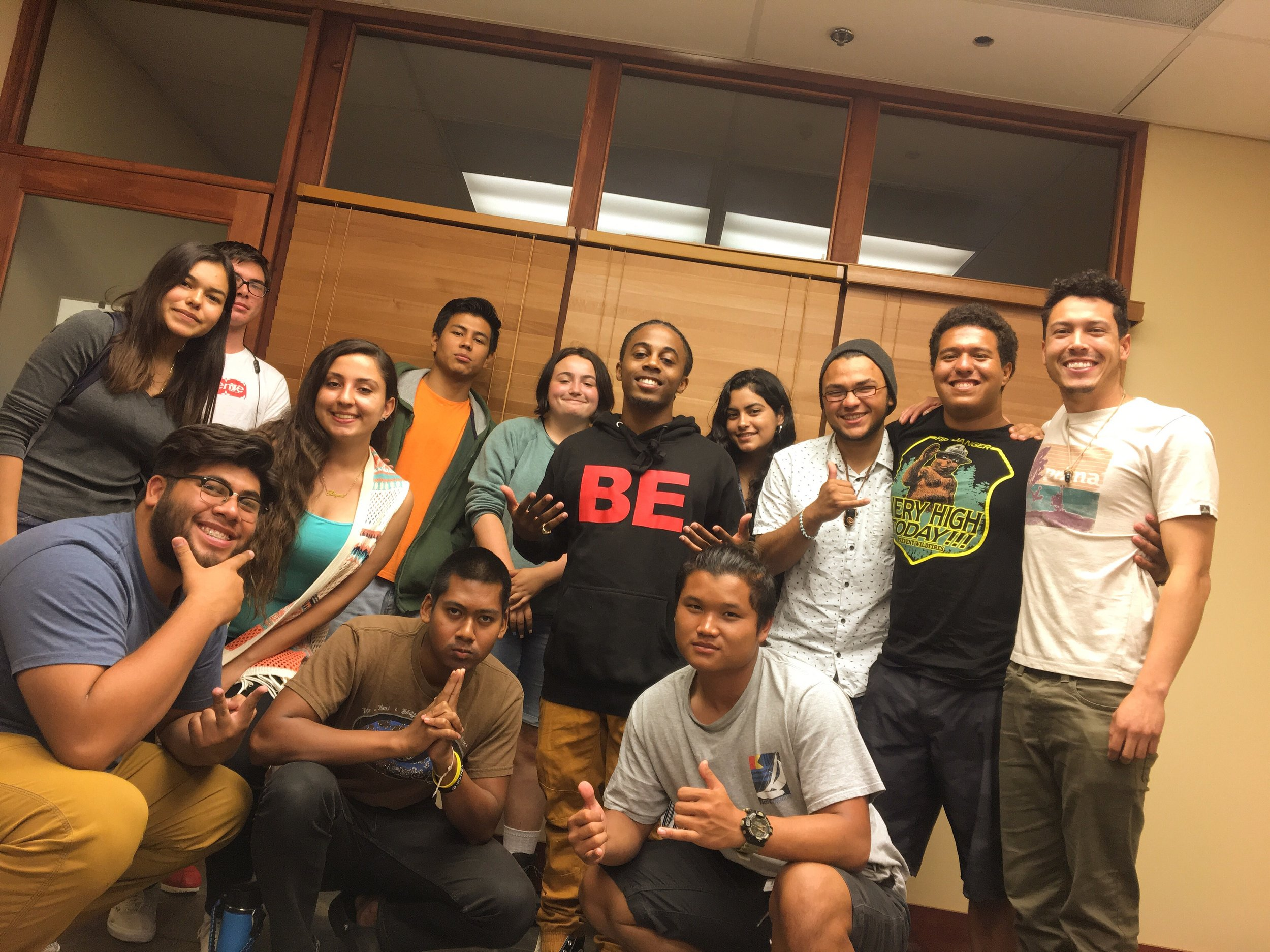 "Instructor Terrance Carter poses with the youth at Outdoor Outreach's final ""BE Your Story"" summer workshop! Throughout Summer 2019, these youth created stories around 'BEing courageous, BEing authentic, and BEing the best version of themselves that they can BE!  To start off the summer right, we joined with the youth at Outdoor Outreach and immediately began to build genuine connections through creative storytelling. At every workshop, these youth consistently shared their stories with brave hearts and firm intentions. Everyone always had something to share that was raw and inspiring. The room was always on 100, the vibe always felt like home, and the storytelling just got better and better each time!"