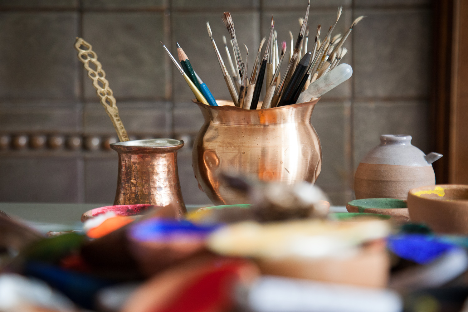 Water containers for mixing and working, an endless supply of brushes, pencils and blades are used to produce such fine detail.
