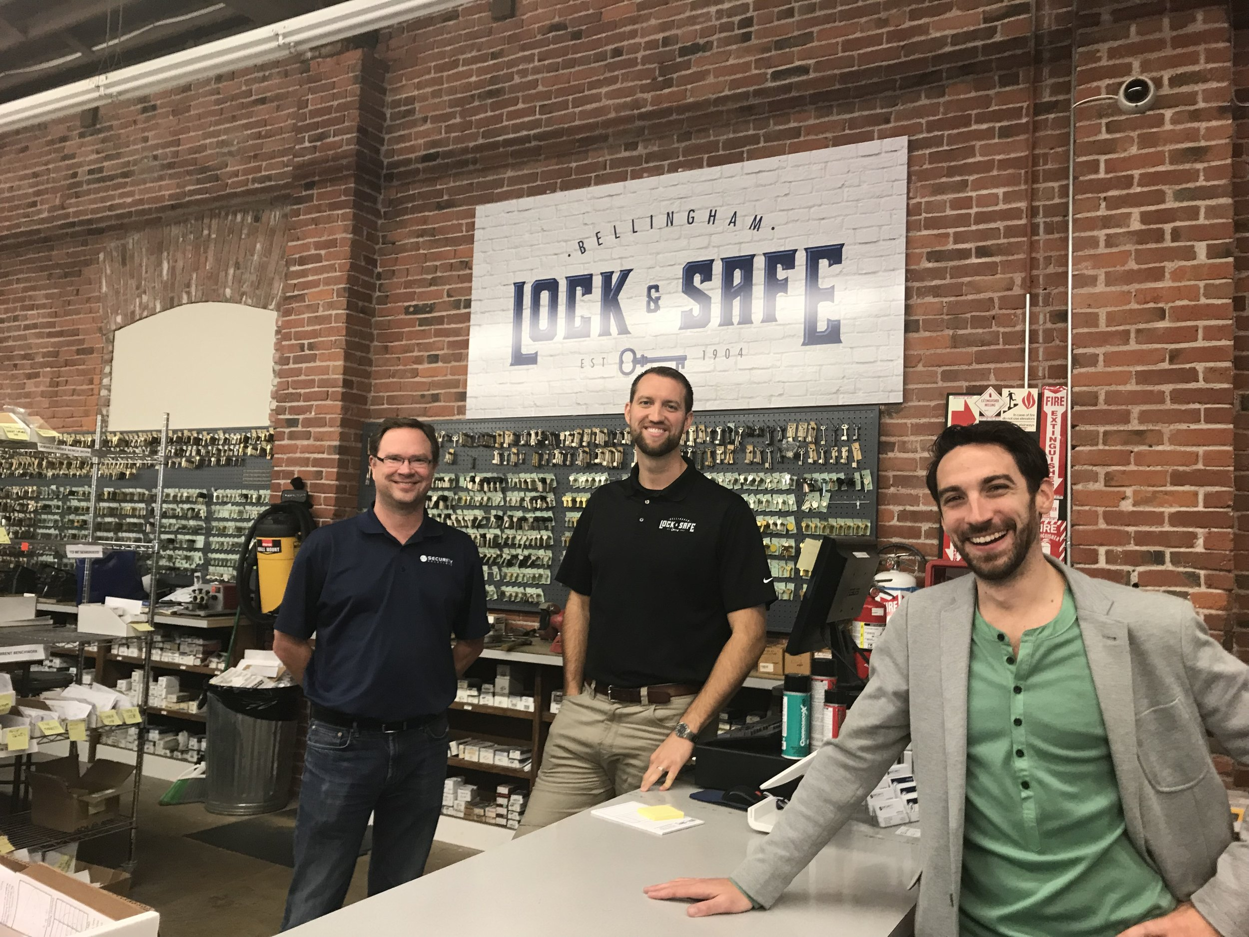 Jamie Vos, left, owner of Security Solutions, Daniel Ford, middle, locksmith manager, and Ray Deck III, right, executive director of Skookum Kids, pose for a picture inside Bellingham Lock & Safe in Bellingham, on Thursday, Oct. 27, 2017.