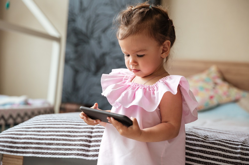 storyblocks-image-of-serious-little-girl-child-indoors-using-mobile-phone-looking-aside_rClxujipcZ.jpg