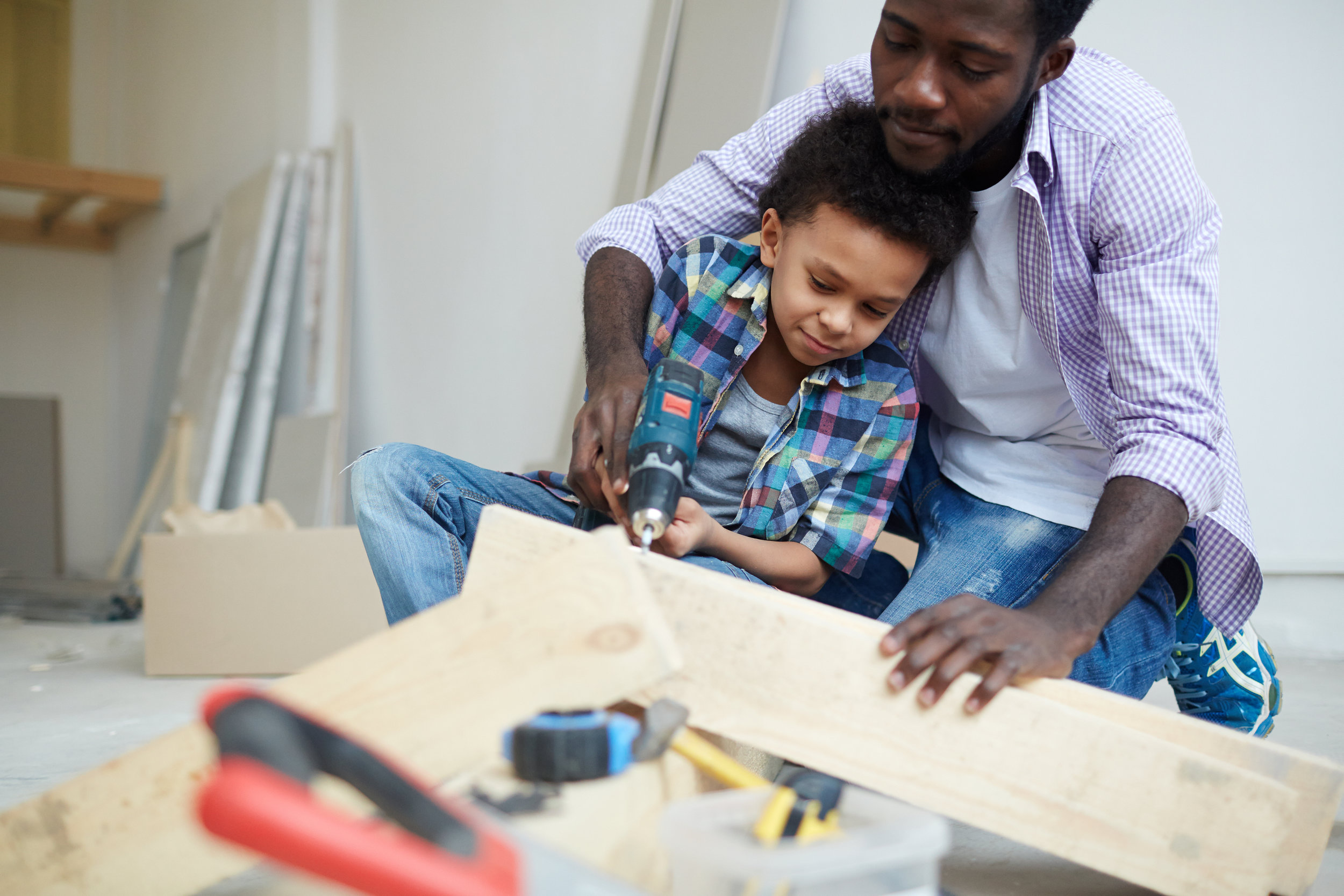 storyblocks-young-man-showing-his-son-how-to-work-with-electric-drill_HUXpoN8w0b.jpg