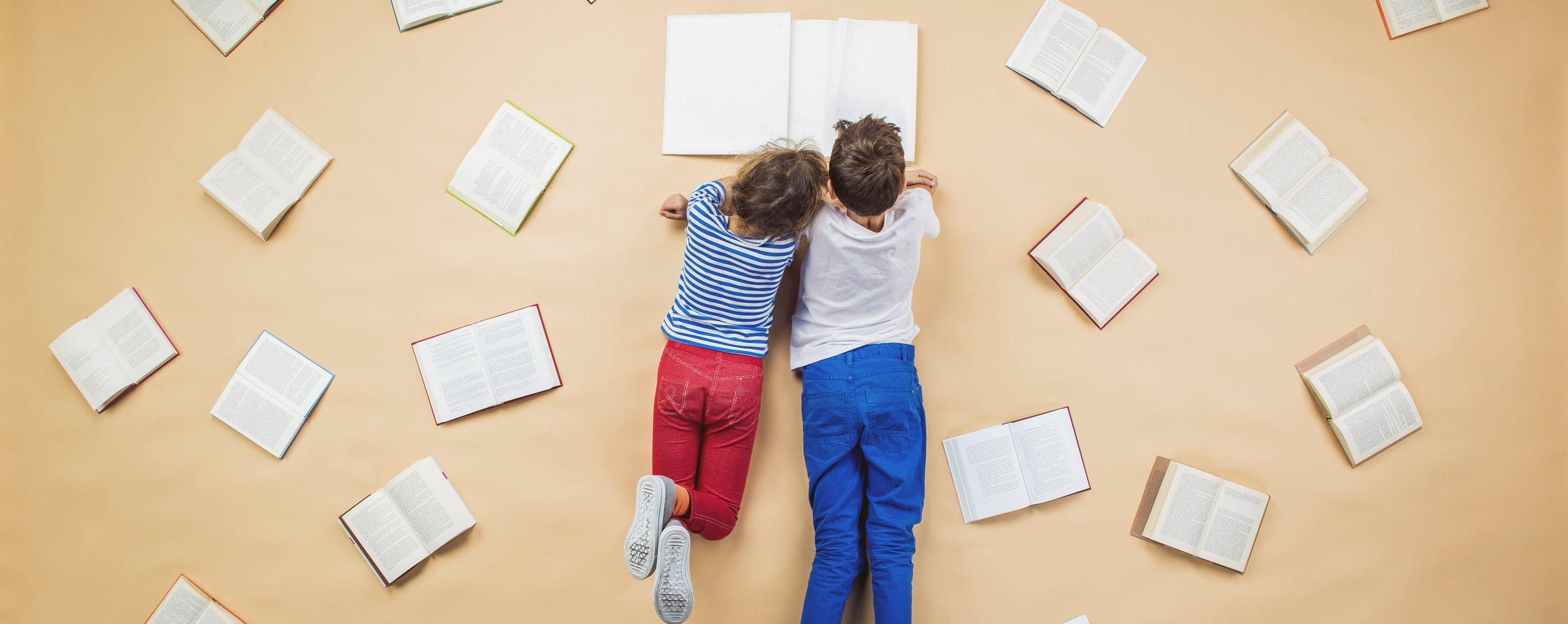 graphicstock-happy-children-are-reading-book-on-the-floor-with-group-of-books-around-them_SAmDFJ2-Z.jpg