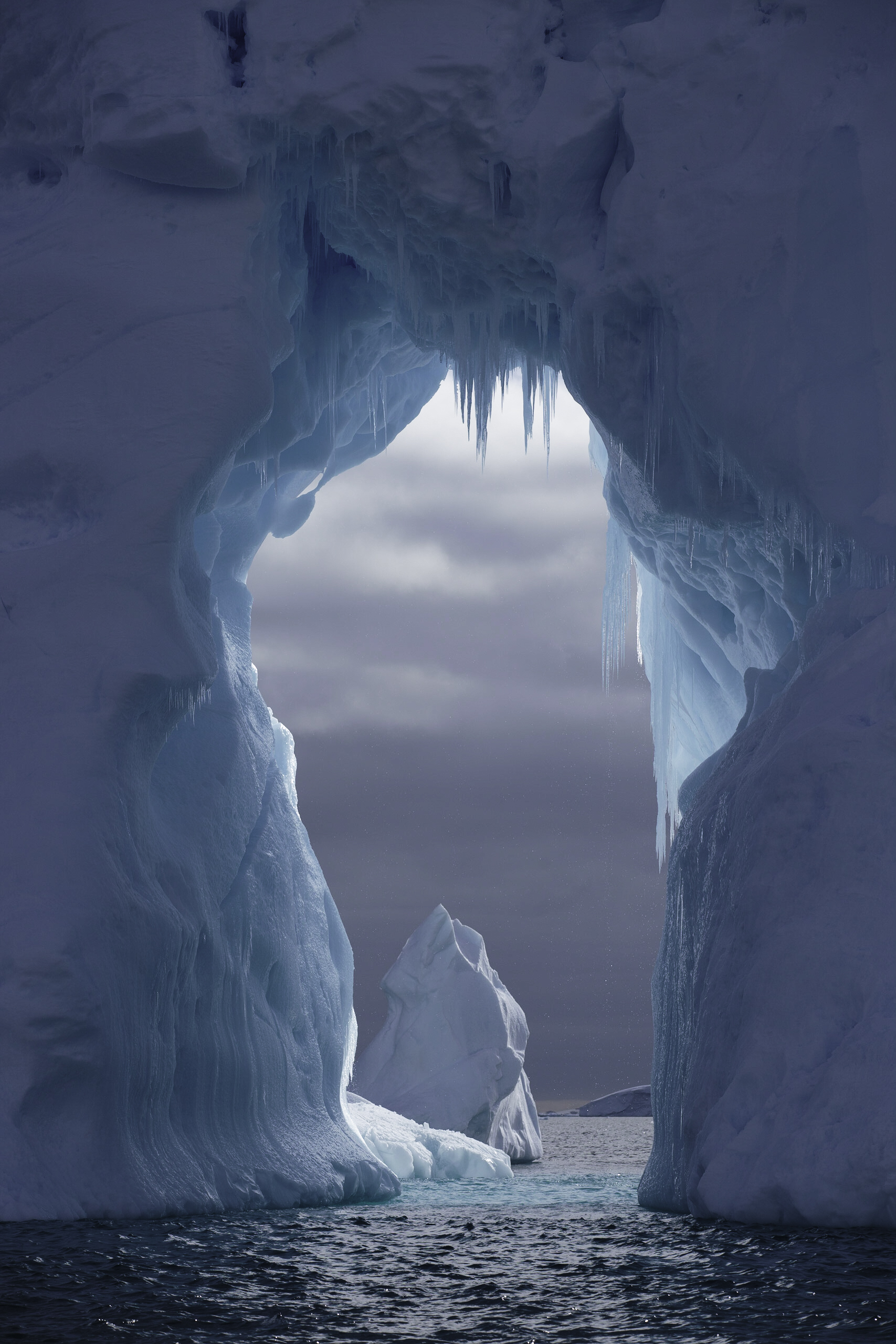 A massive ice arch is formed in a floating iceberg —large enough to drive a boat through.