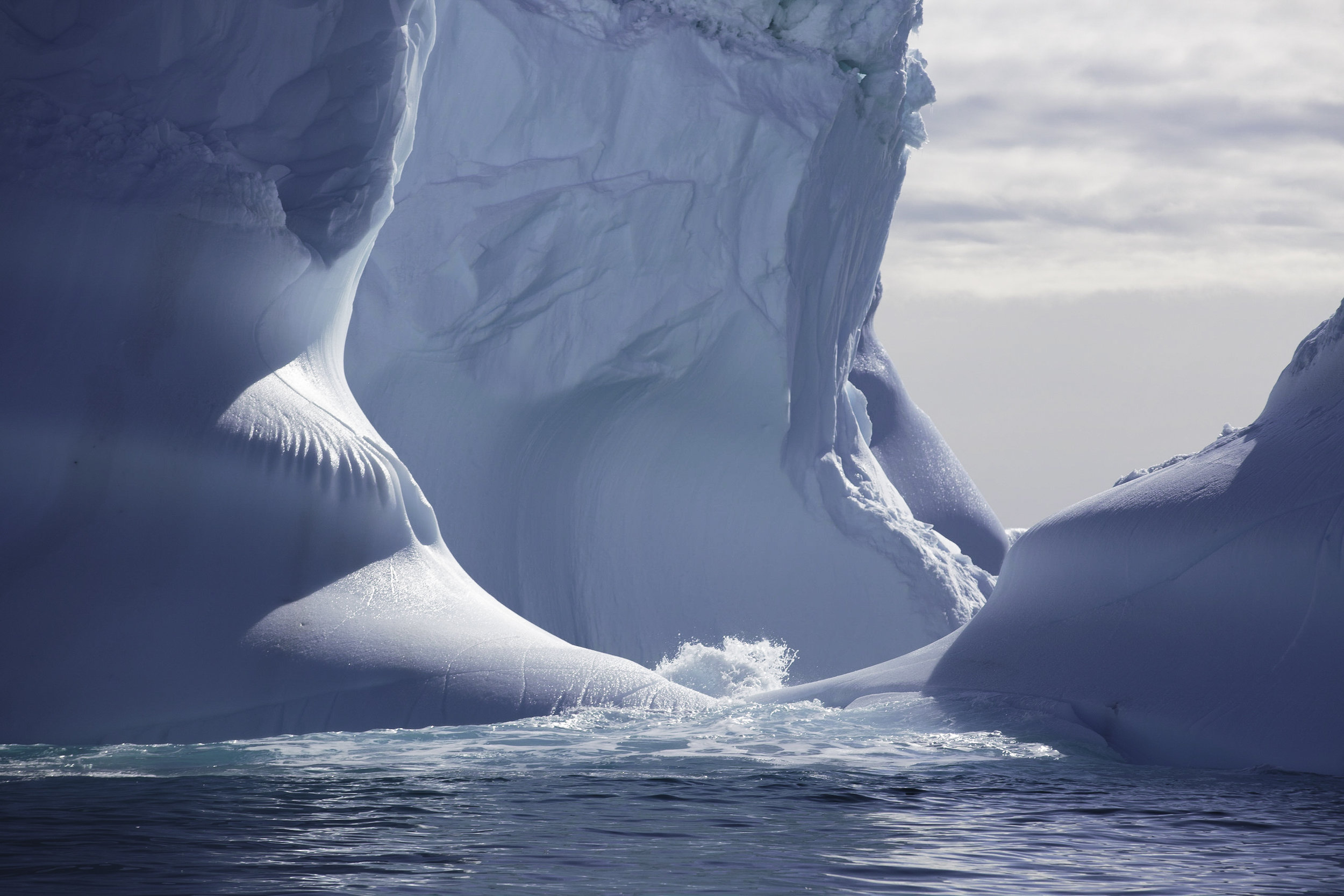 A wave splashes in and out of a large pool formed in the base of four towers protruding up from a large iceberg.