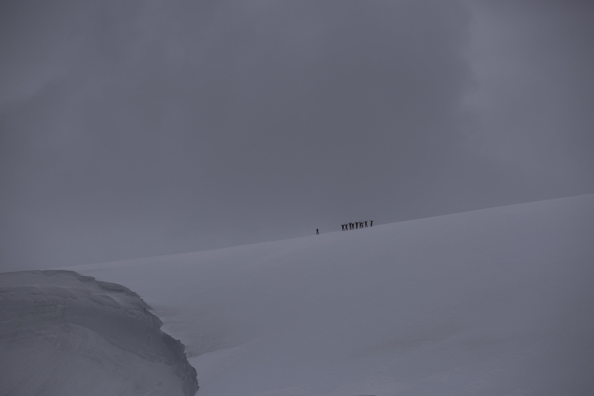 A group of snowshoers from the snowshoe program hike around on a glacier above Port Lockroy.