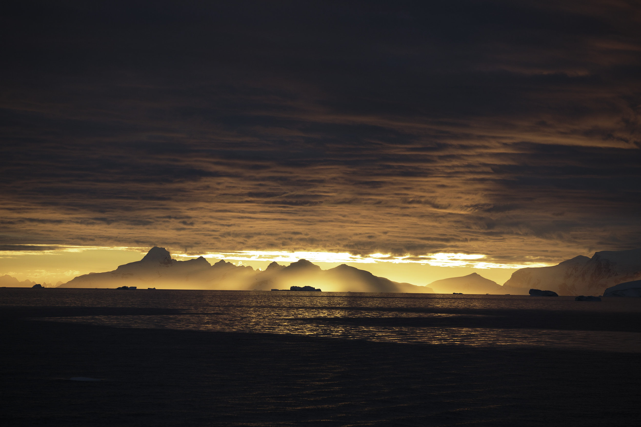 Icebergs, mountains and low cloud cover make for a special sunset.