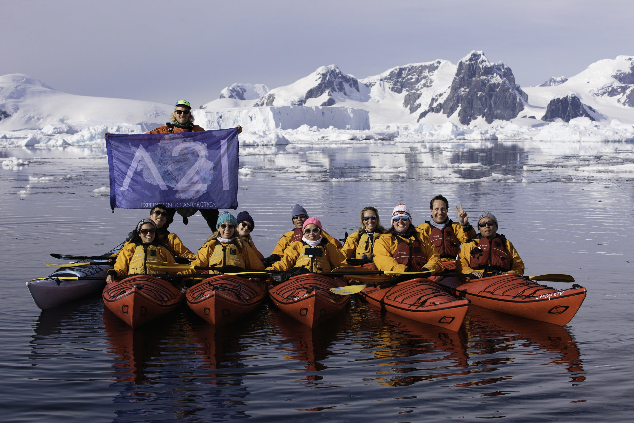Kayakers posing with the Antarctica 21 flag.