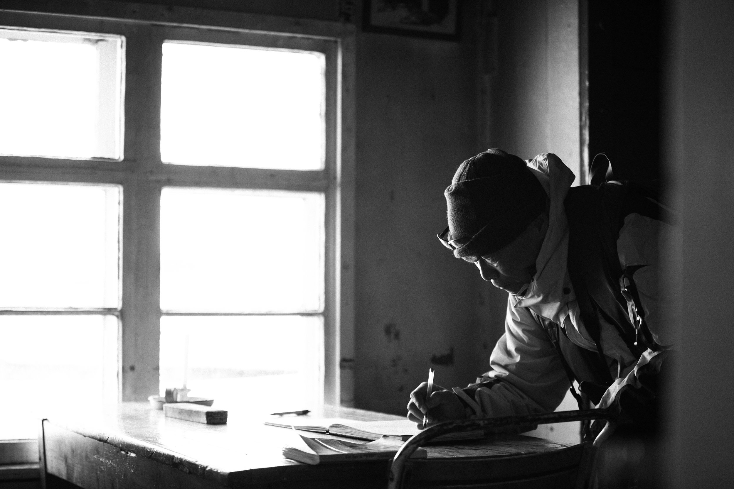 A guest signs the visitor logbook at historical Wordie House in the Argentine Islands.