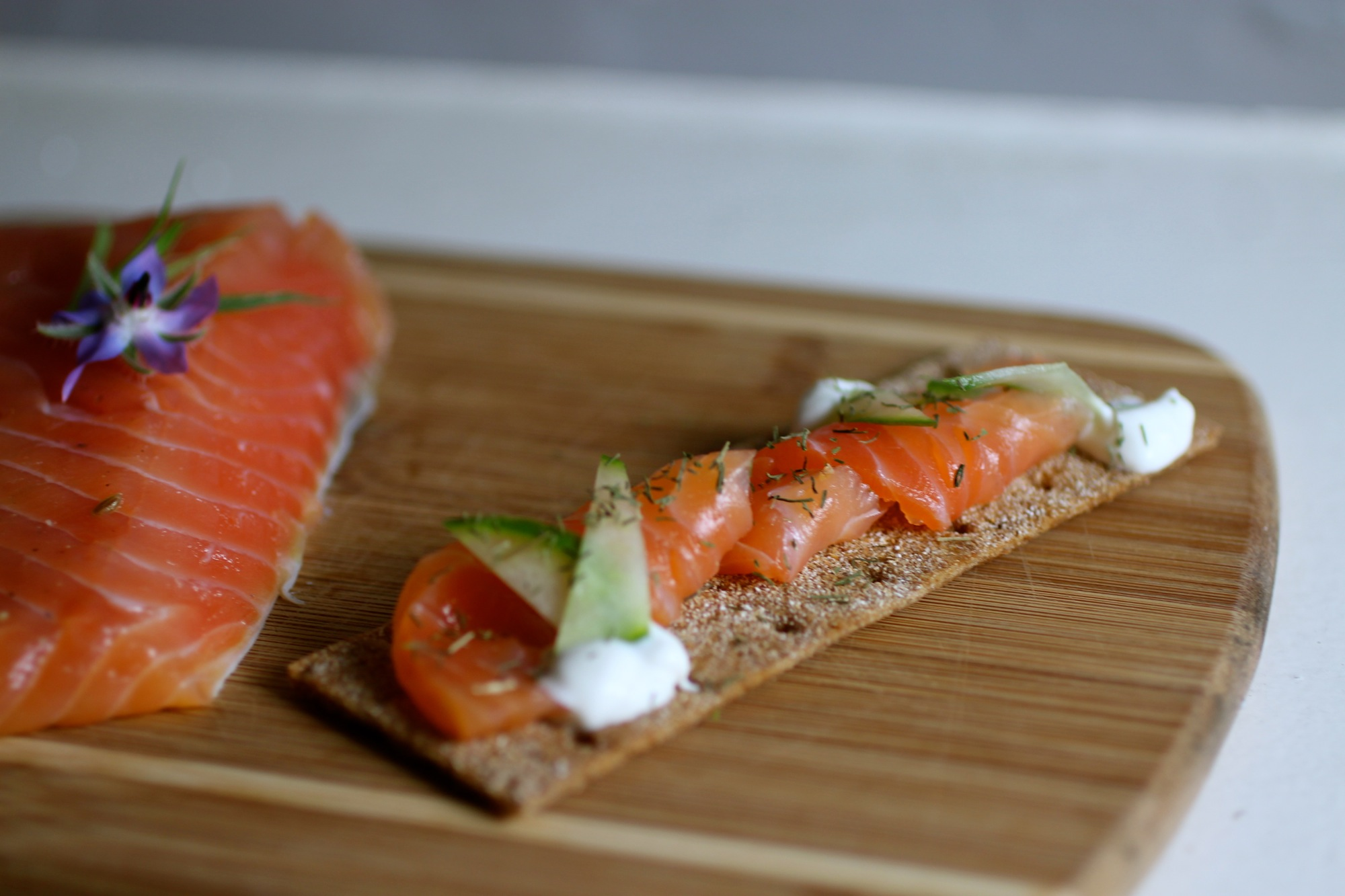 Gravlax with crème fraîche, cucumber, and dill on rye cracker.