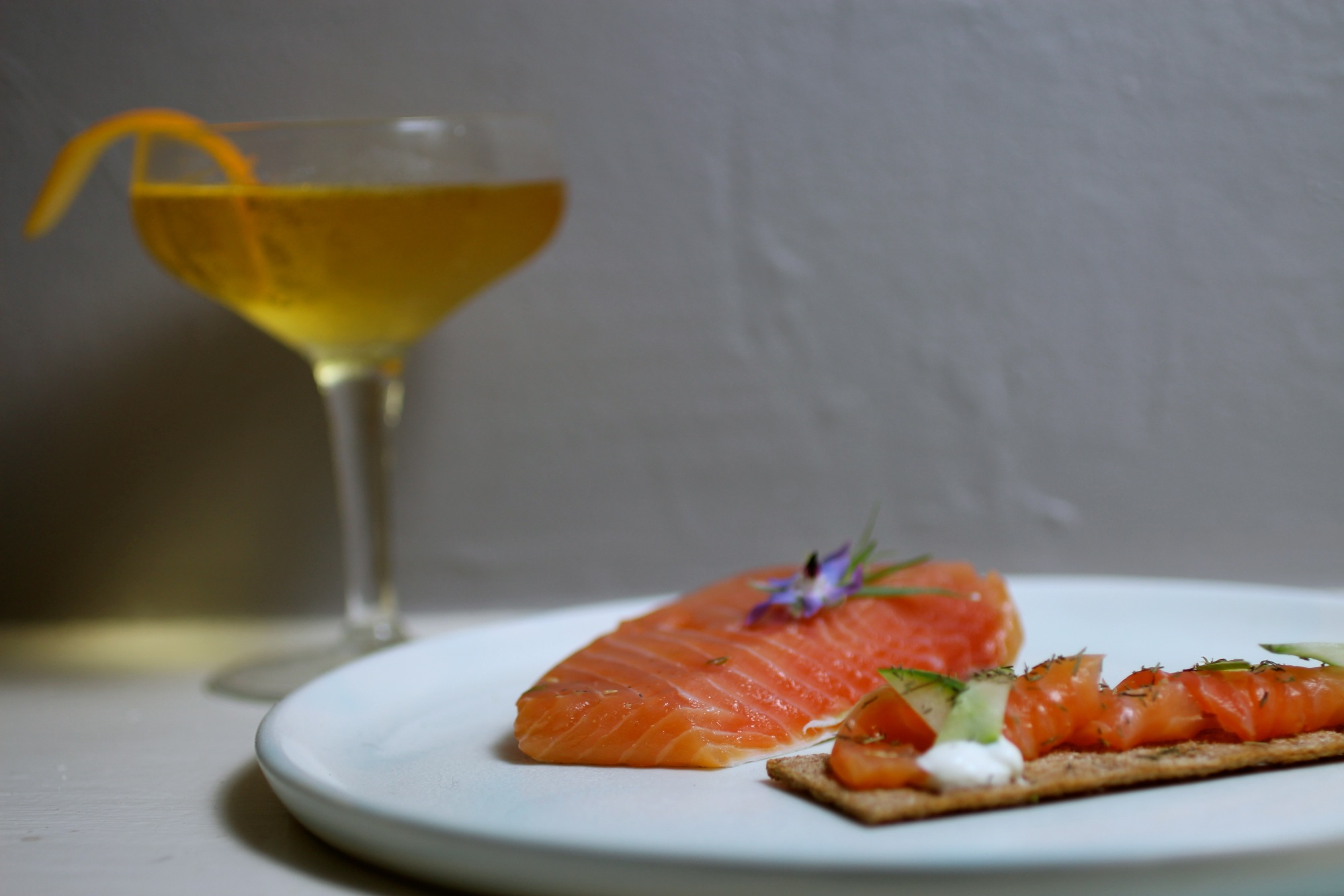Gravlax pairs perfectly with rye crackers, cucumber, aquavit cocktails, and borage flower garnish.
