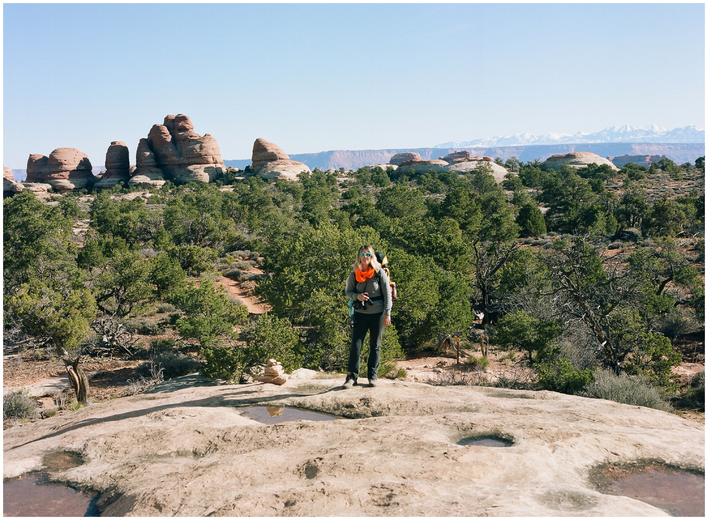 Sonja on the hike out of Elephant Canyon on a warm spring day. La Sal Mountains in the distance. Film photography by Max Salzburg of Sonja K Photography.