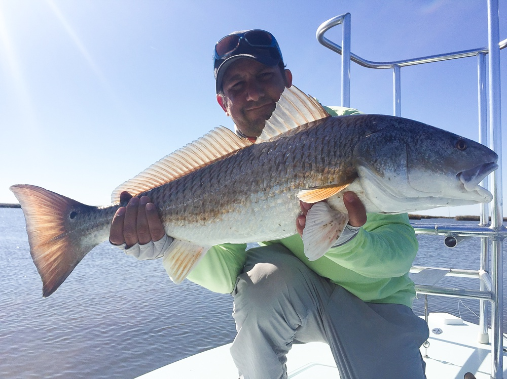 Max Salzburg with a large bull redfish in the Louisiana marshes outside of Port Sulphur.