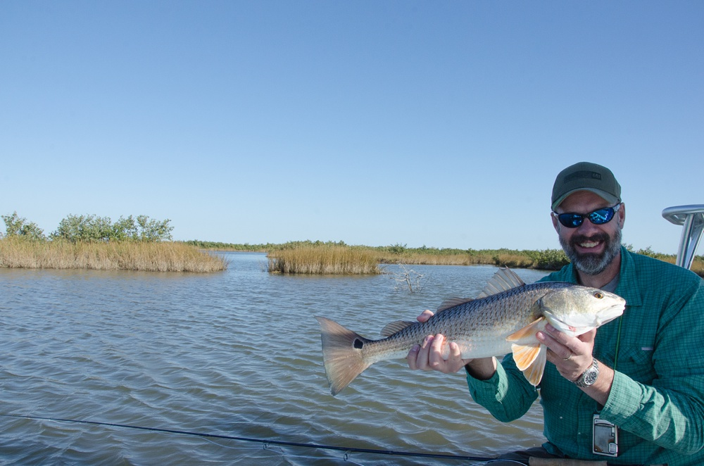 Jerry Caldwell with a nice redfish in the Louisiana marsh near Port Sulphur. Fly fishing travel photography by Max Salzburg of Sonja K Photography.