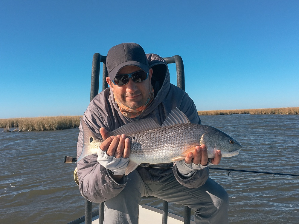My first redfish of the trip in the Louisiana marsh near Port Sulphur. Fly fishing travel photography by Max Salzburg of Sonja K Photography.