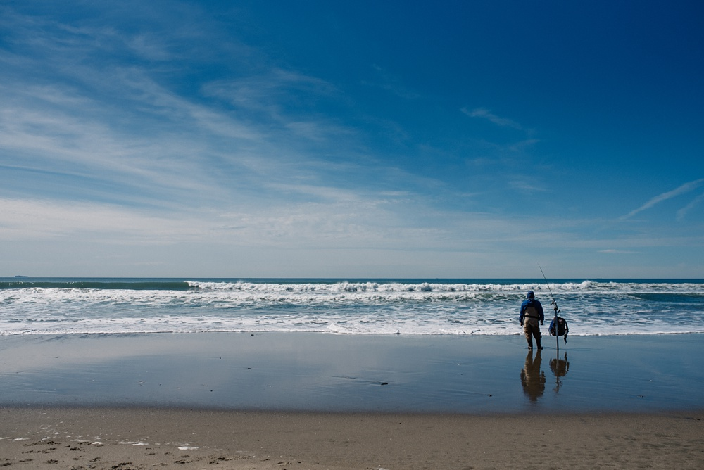 A man fishes from the beach at Fort Funston outside of San Francisco, California. Travel photography by Sonja Salzburg of Sonja K Photography.