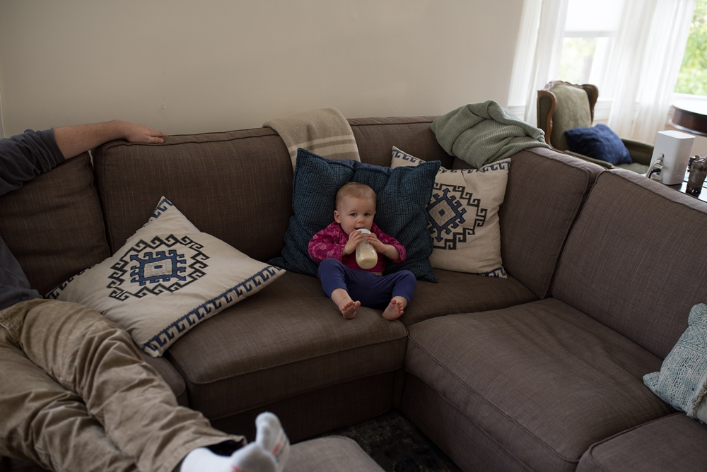 Lydia hangs out on the couch at her home in Oakland, California. Family travel photography by Sonja Salzburg of Sonja K Photography.