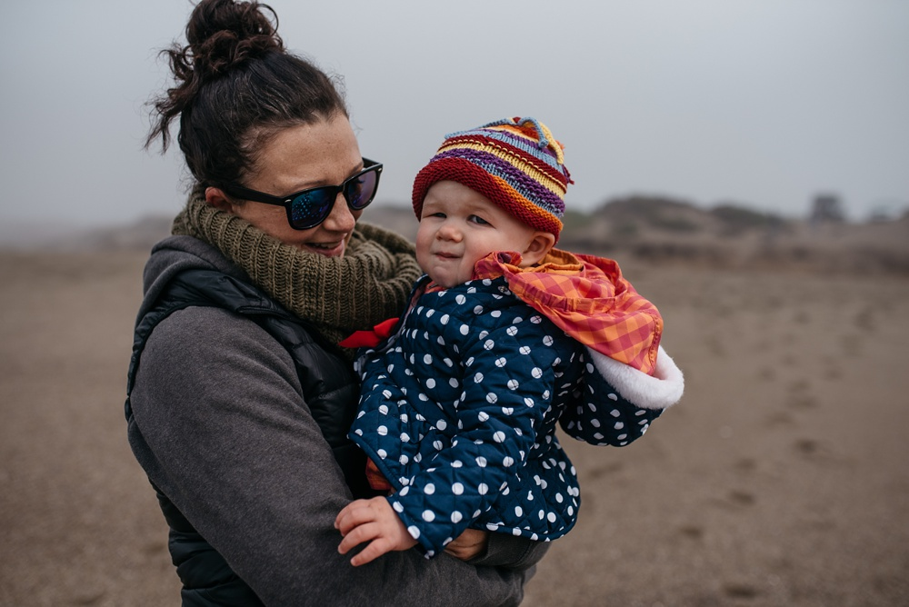 A mom and her daughter at South Beach at Point Reyes National Seashore in California. Family portrait photography by Sonja Salzburg of Sonja K Photography.
