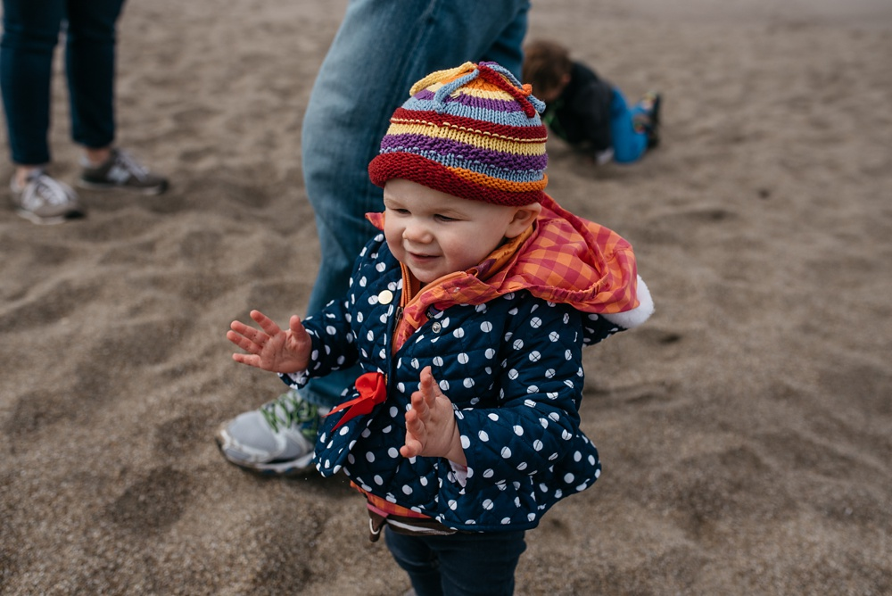 A child plays at South Beach on Point Reyes National Seashore. Family travel portrait photography by Sonja Salzburg of Sonja K Photography.