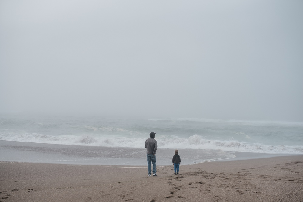 A father and son on South Beach at Point Reyes National Seashore in California. Family travel portrait photography by Sonja Salzburg of Sonja K Photography.
