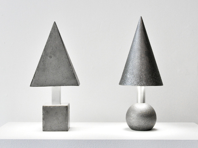CAST CONCRETE & ALUMINUM LAMPS - Designed as an exploration of familiar primary forms in new materials and of the interplay between darkness and light. A pyramid shade on a cube base was cast in concrete and a cone shade on a cylinder base was cast in aluminum.Sizes:Pyramid/Cube: 14cm L x 14cm W x 28cm HCone/Cylinder: 14cm diameter x 28cm HAvailable by special orderphoto by Caley Tessier
