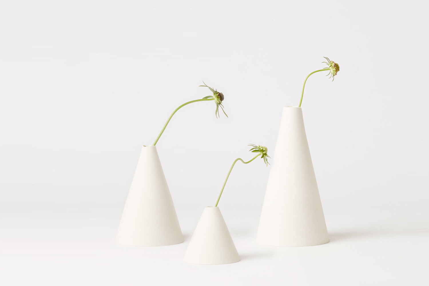 CONE VASES - This series is an interpretation of the classic geometric cone form, thrown on the potter's wheel; their raw strength highlighted by the bare, unglazed exterior and rough rim.Sizes: ranging from 6cm diameter x 9cm H to 10cm diameter x 18cm HAvailable by special orderphoto by Blaise Misiek