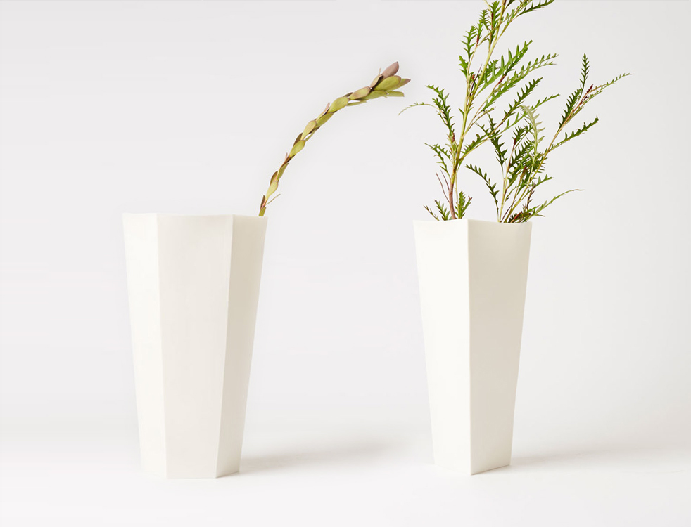 HEX AND TRIANGLE VASES - Made in extremely thin, translucent slip-cast porcelain, each piece begins as a pure geometric shape—hexagon or triangle—which becomes distorted as the porcelain fires at high temperatureSizes: approximately 15cm L x 15cm W x 25cm HAvailable by special orderphoto by Blaise Misiek