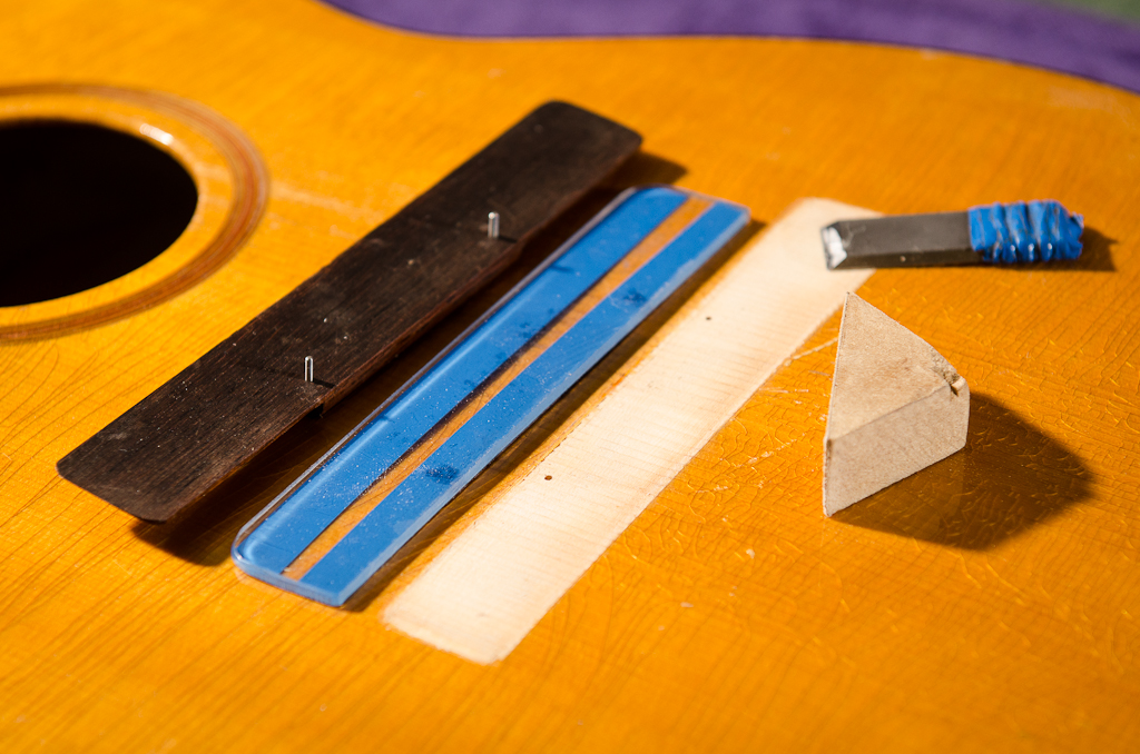 Preparing for reglue: (left to right) bridge with locating pins, scraping/sanding safety guide, scraper and sanding block