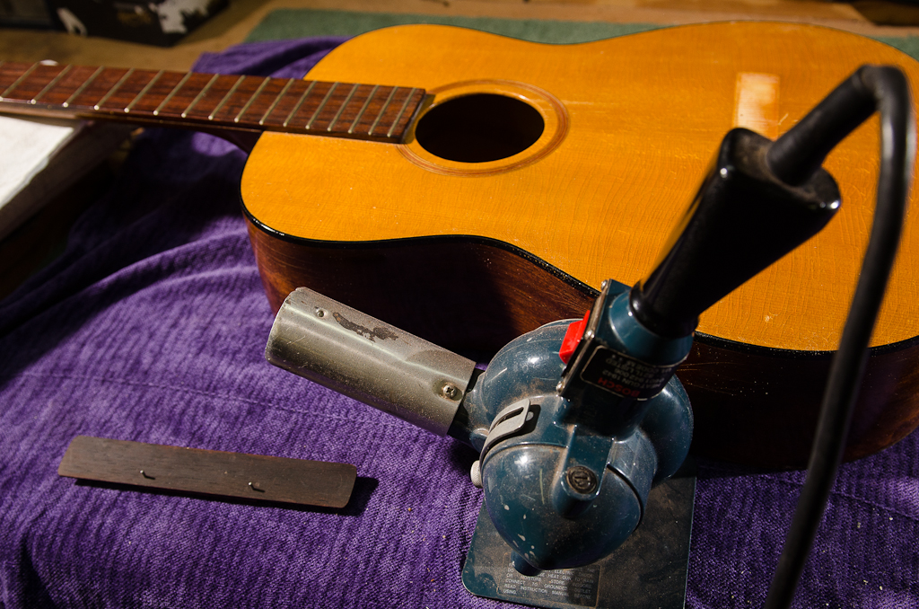 Heat gun is used to warm up the bridge and soundboard footprint to extend hot hide glue working time