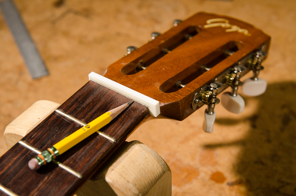 A pencil flattened on-axis projects the plane of the frets onto the new nut, along with marking the edges to be trimmed