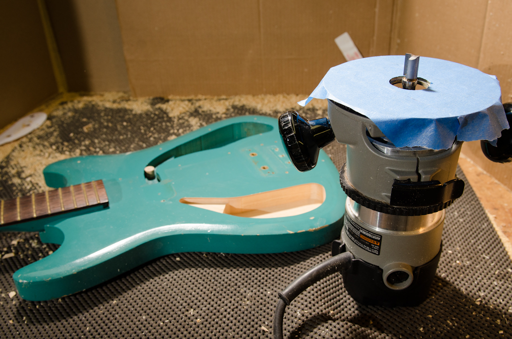 I switch to a bearing router bit to finish off the cavity. The template is removed and the bearing will flush-trim off of the established cavity walls. I tape the base of the router to help protect the guitar's finish.