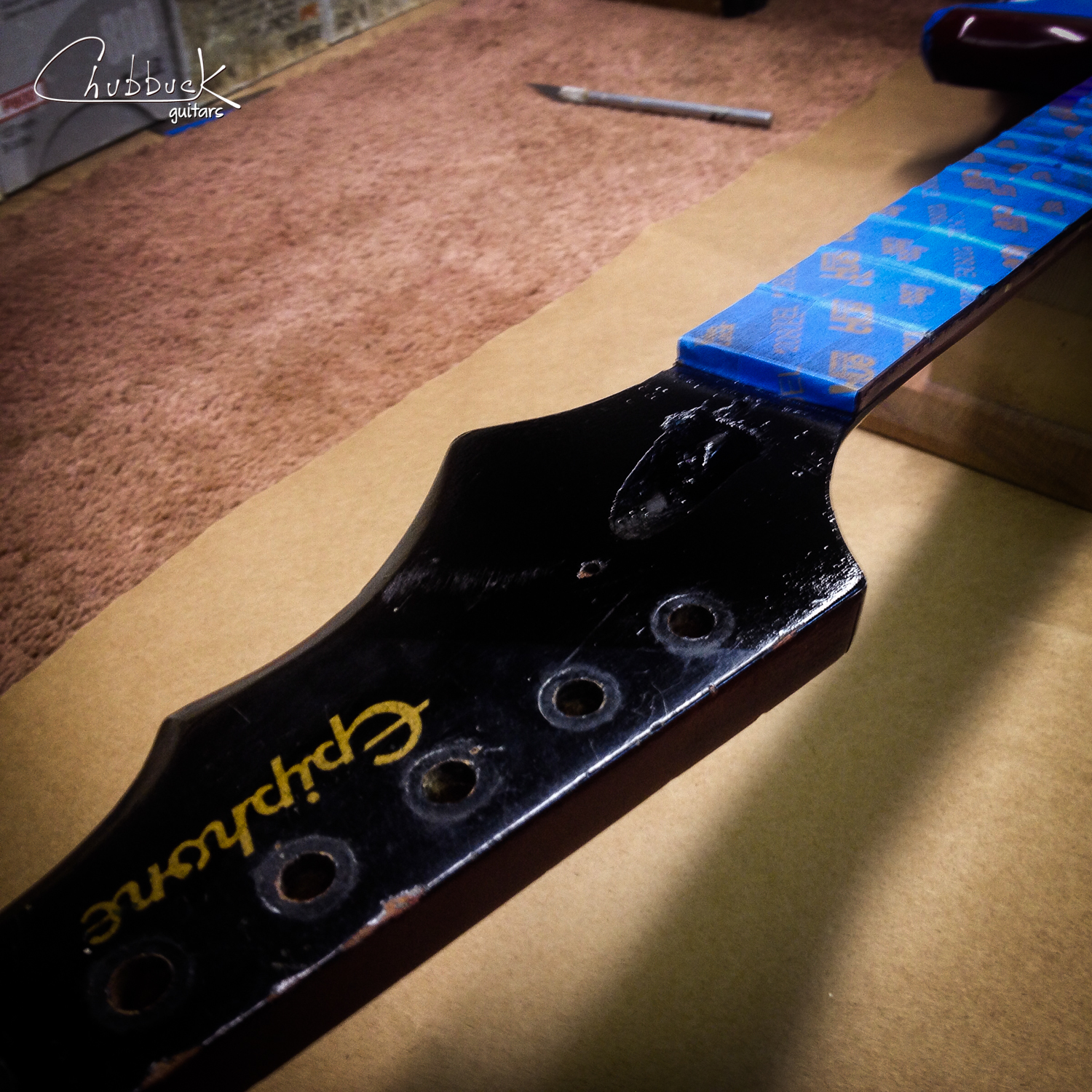 """Fresh out of the booth with the repairs blacked out. I had to be careful to not get overspray near the silkscreened """"Epiphone"""" logo. This logo is proud of the surrounding finish so any sanding or buffing would risk burning through."""