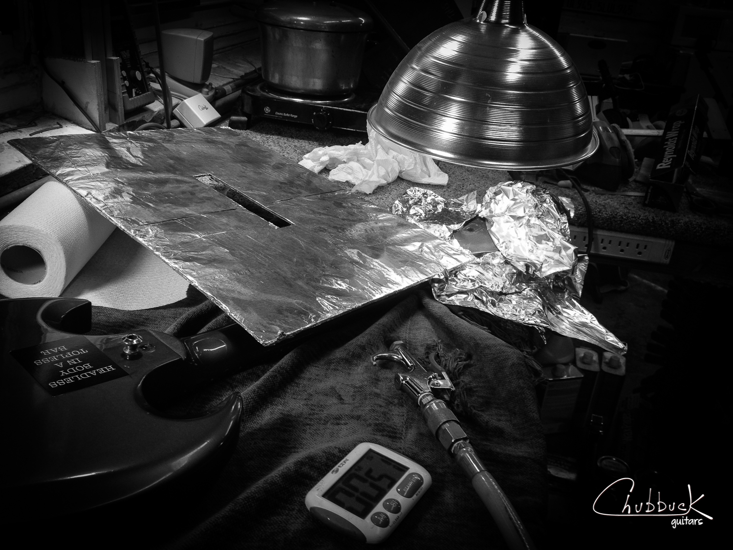 The break was only partially open.  I needed to apply heat and steam to re-break the headstock.  An ifrared heat lamp bulb was used for dry heat and in the background is my neck-reseting pressure pot rig that I used to apply hot steam to the joint.