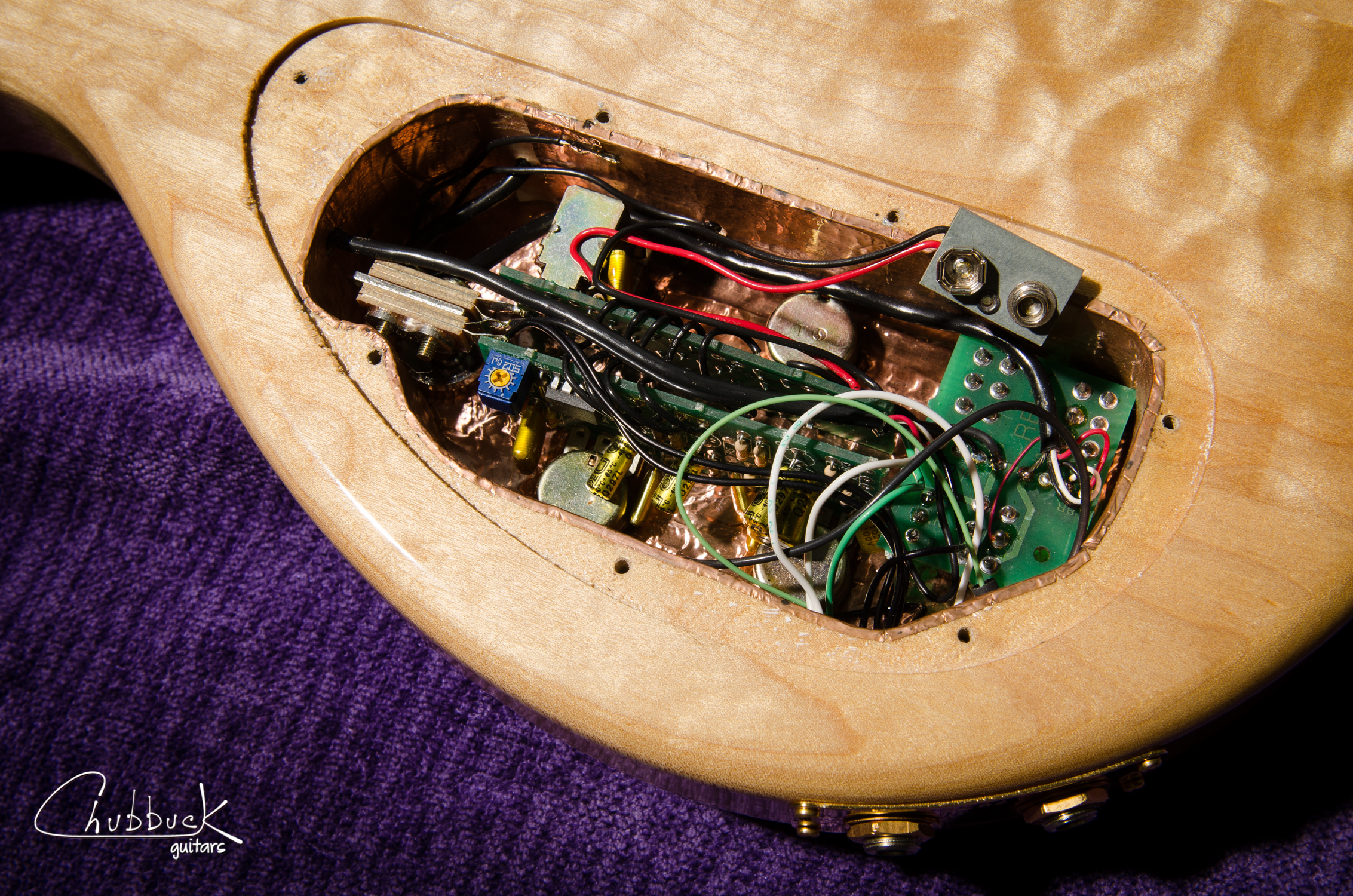 A look inside the control cavity at the active circuit. The controls: neck volume, neck tone, bridge volume, bridge tone, coil taps for each pickup and a phase switch when running both pickups. Note the stereo output jacks to split the signal from each pickup. This will all be removed and converted to passive and mono.