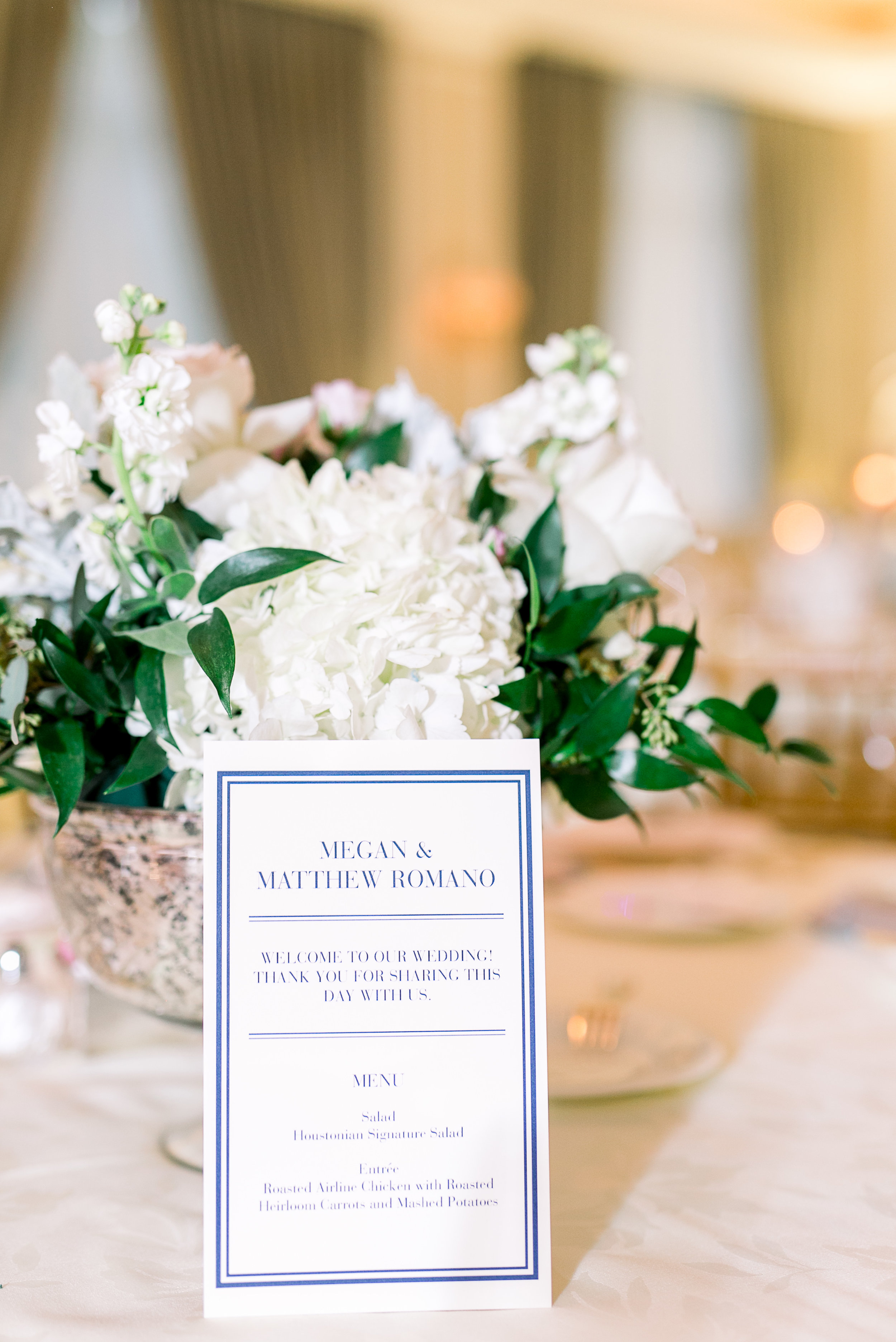 Blue and White menu card in front of a white and blush floral centerpiece