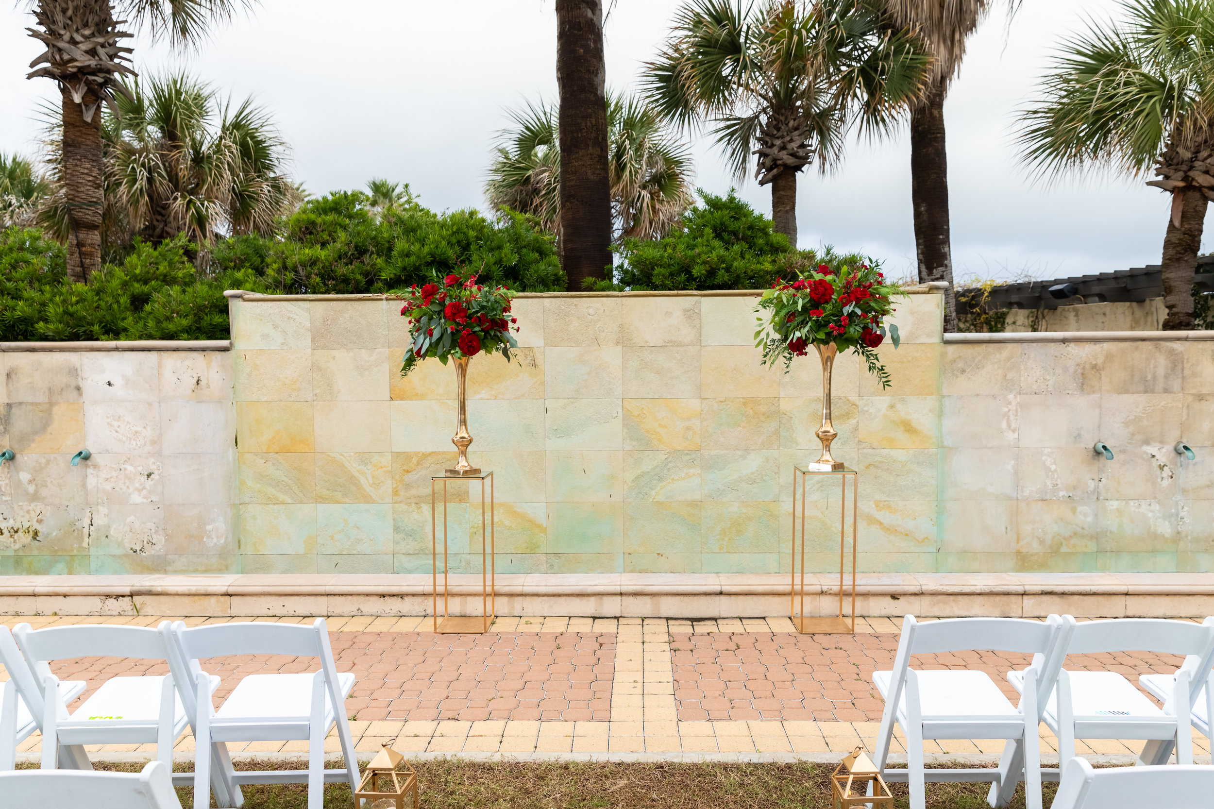 Gold framed columns for a ceremony backdrop with red floral at Hotel Galvez