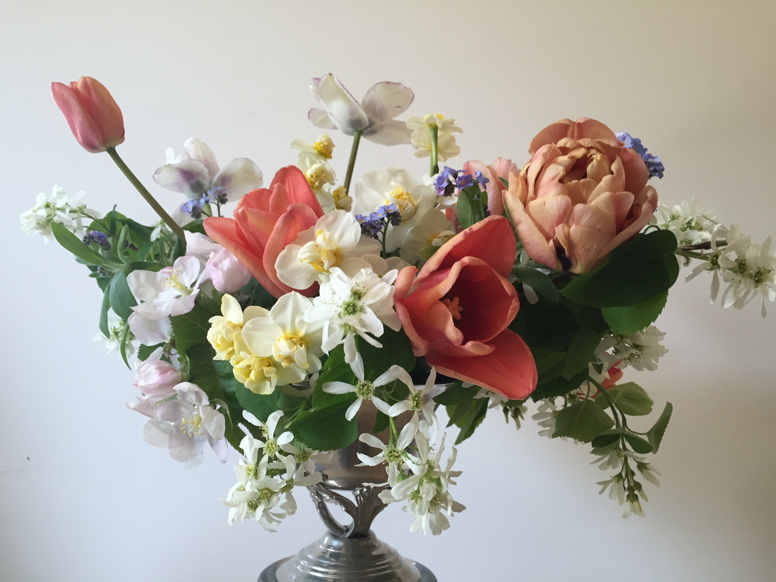 A centrepiece arrangement featuring 'Apricot Foxx,' 'Belle Epoque' and 'Shirley' tulips, 'Cheerfulness' and 'Minnow' daffodils, apple and saskatoon branches, forget-me-nots