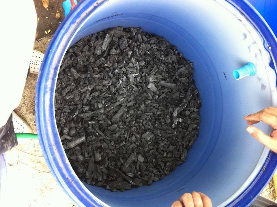 燒製好的木炭,倒入大桶中,成為天然的濾芯。