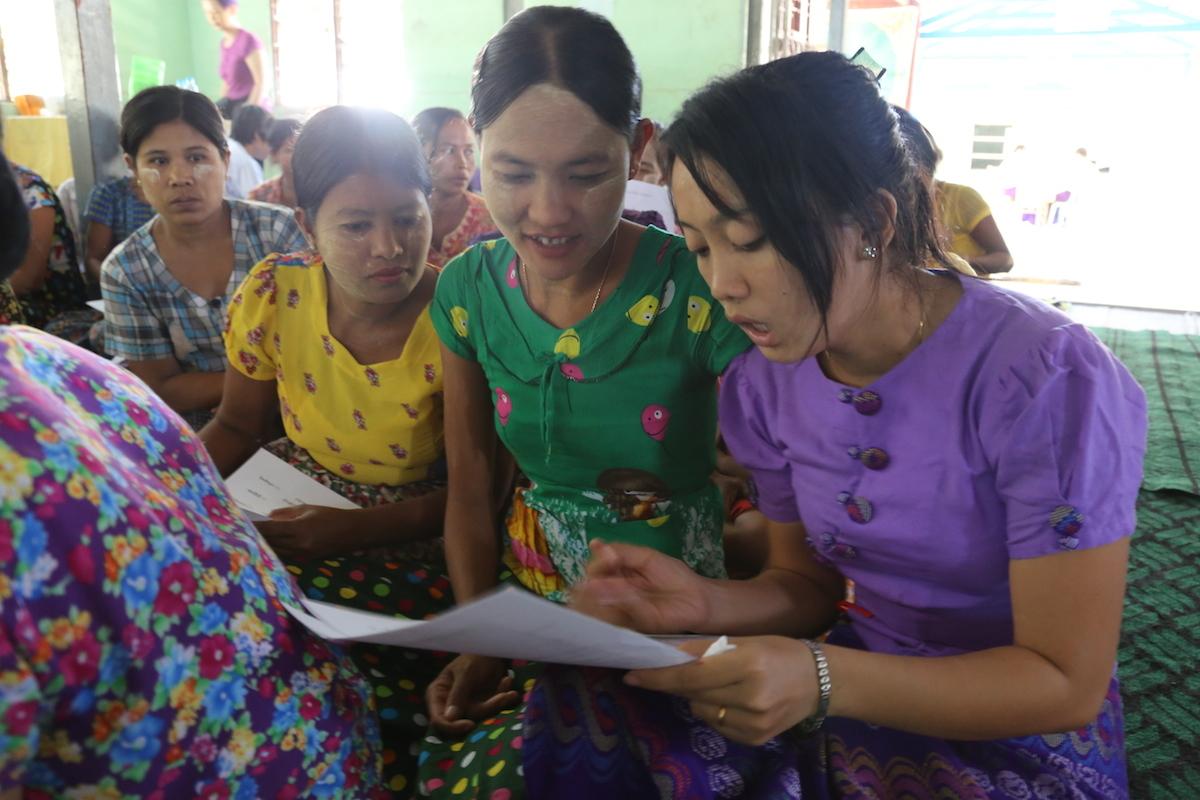 寧佩松(右)在家長衛教活動前前引導學童家長填表,評估他們的衛生觀念程度。(攝影╱陳阿凱)