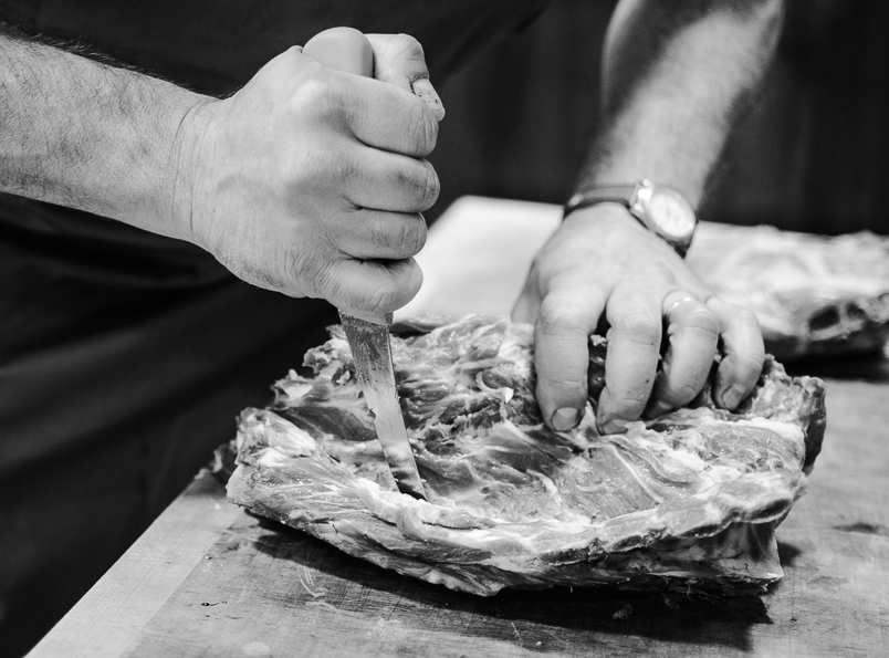 A butcher trimming a joint of meat