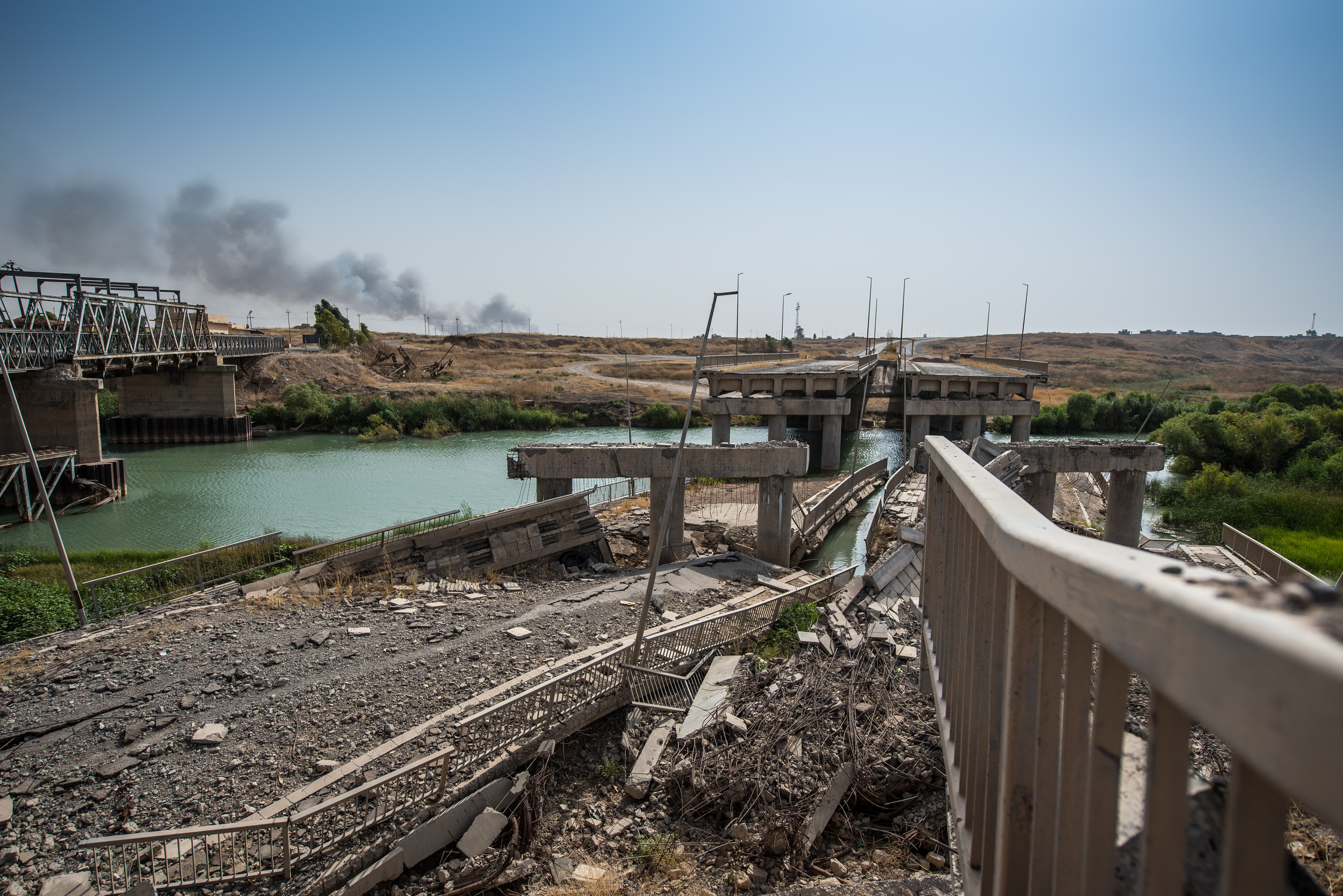 A highway bridge between Mosul and Erbil destroyed by the fighters of the Islamic State on their retreat. In the background the explosion and smoke form a coalition airstrike is visible.