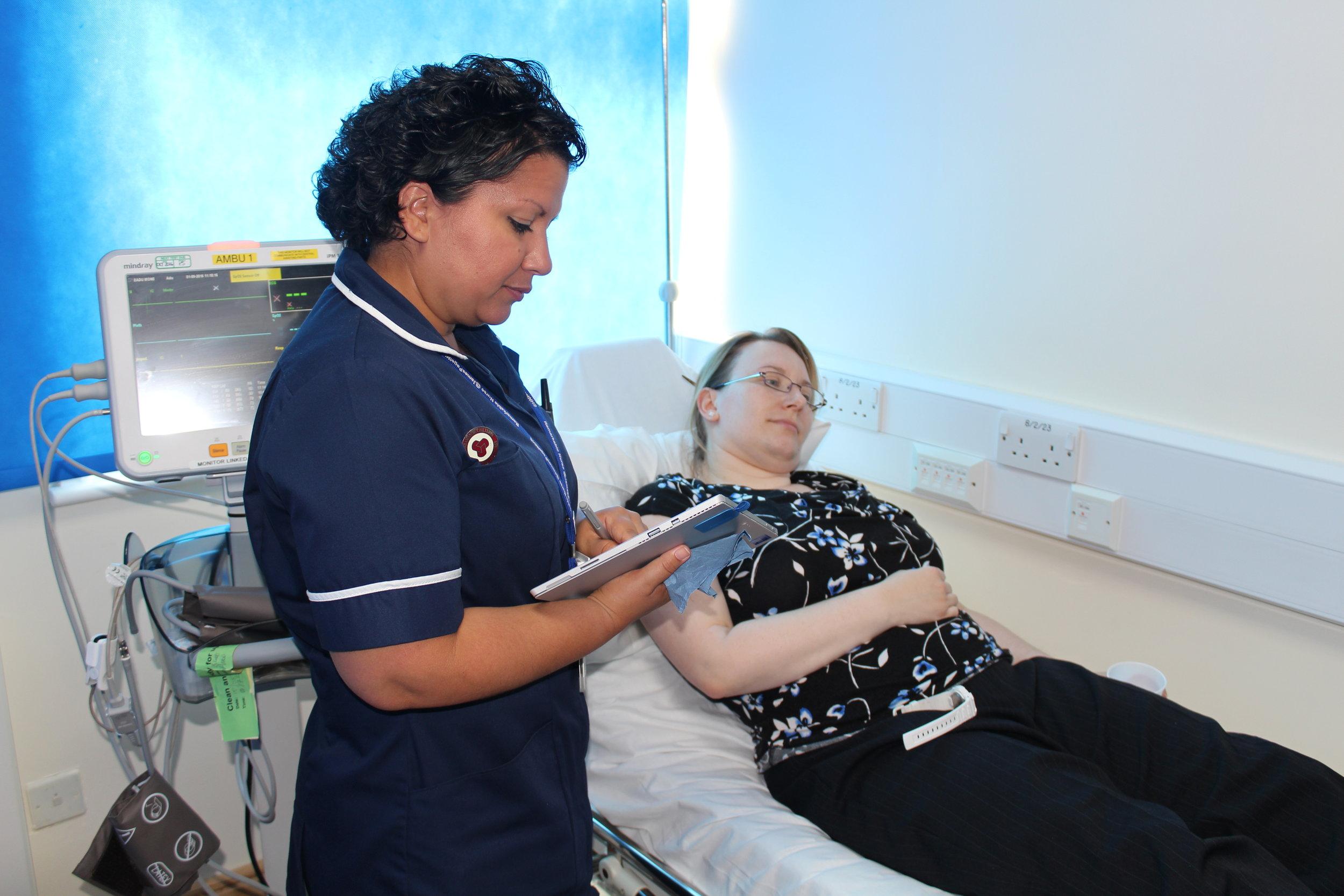 JPUH Ambulatory Care Unit Nurse Practitioner Karen Foden taking case notes on a patient (Photography by Laura Crisp)