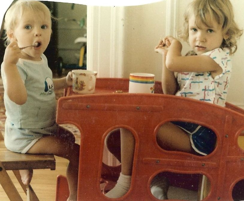 Alexay, my sister, on the left dining with me on the right dining in our convertible high-chair/table (circa 1986ish)