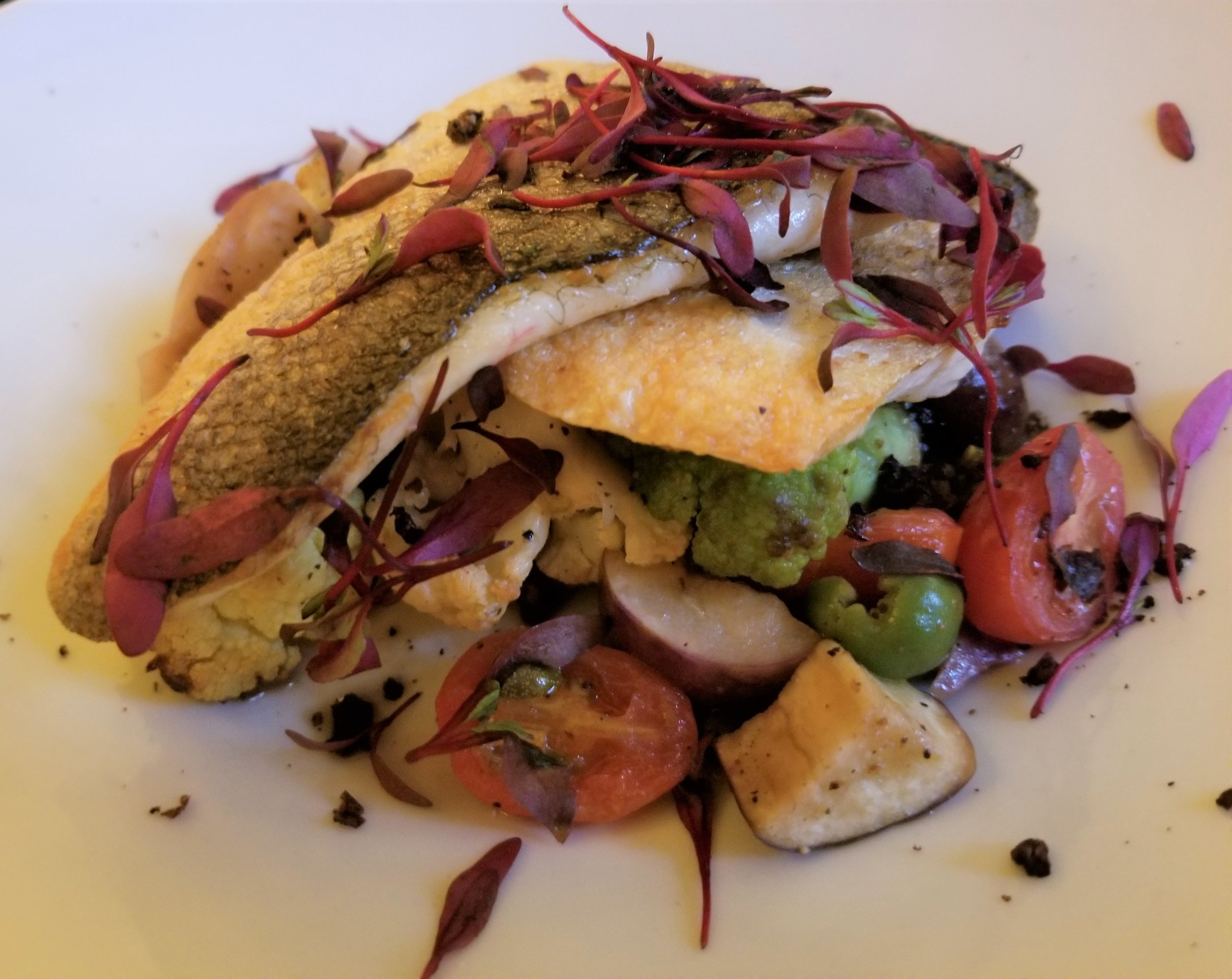 Branzino with rainbow cauliflower, eggplant, caper berries, grape tomatoes, Kalamata olives