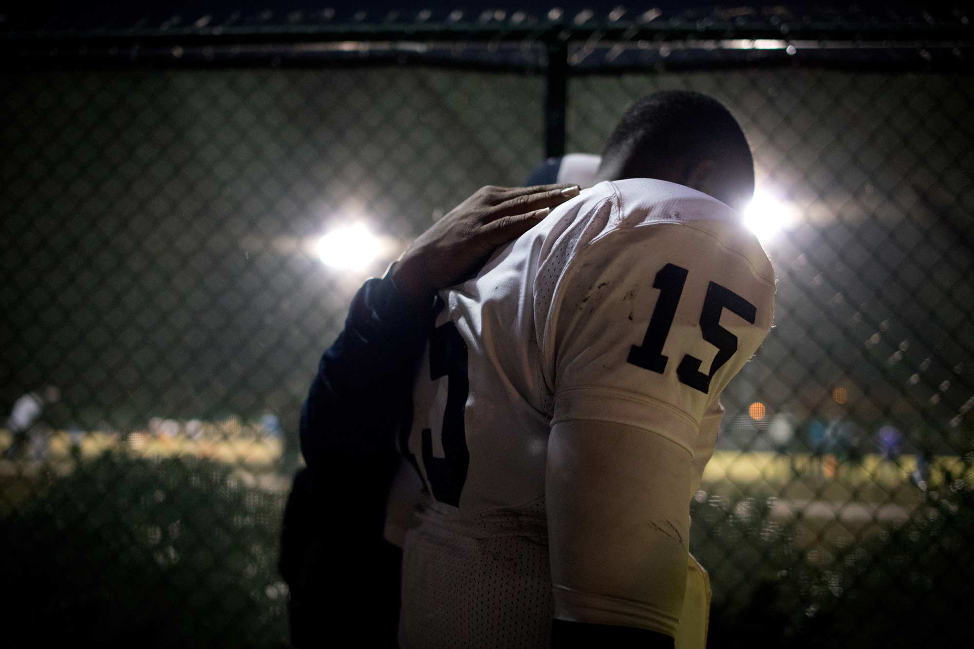 "Coach Kerry Bacon takes a quiet moment with quarterback Nas Forte-Ferguson. Hillside's lost against Knightdale, 16-15, ended their season and crushed any dreams of a state championship. Head Coach Antonio King addressed the tearful team, ""It hurts like hell. It's supposed to, if you're here for the right reasons. I love each and every last one of you."""