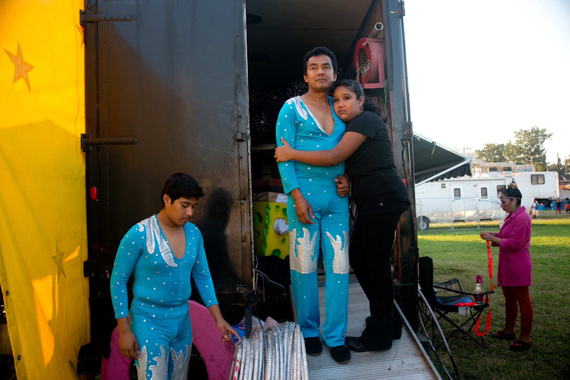 Romario Perez (left), 15, and his father Memo prepare to perform together on the Giant Space Wheel of Destiny. Memo, Romario, and Romario's sister Belgica (third from left), make up one of the two families that currently perform with the Star Family Circus.