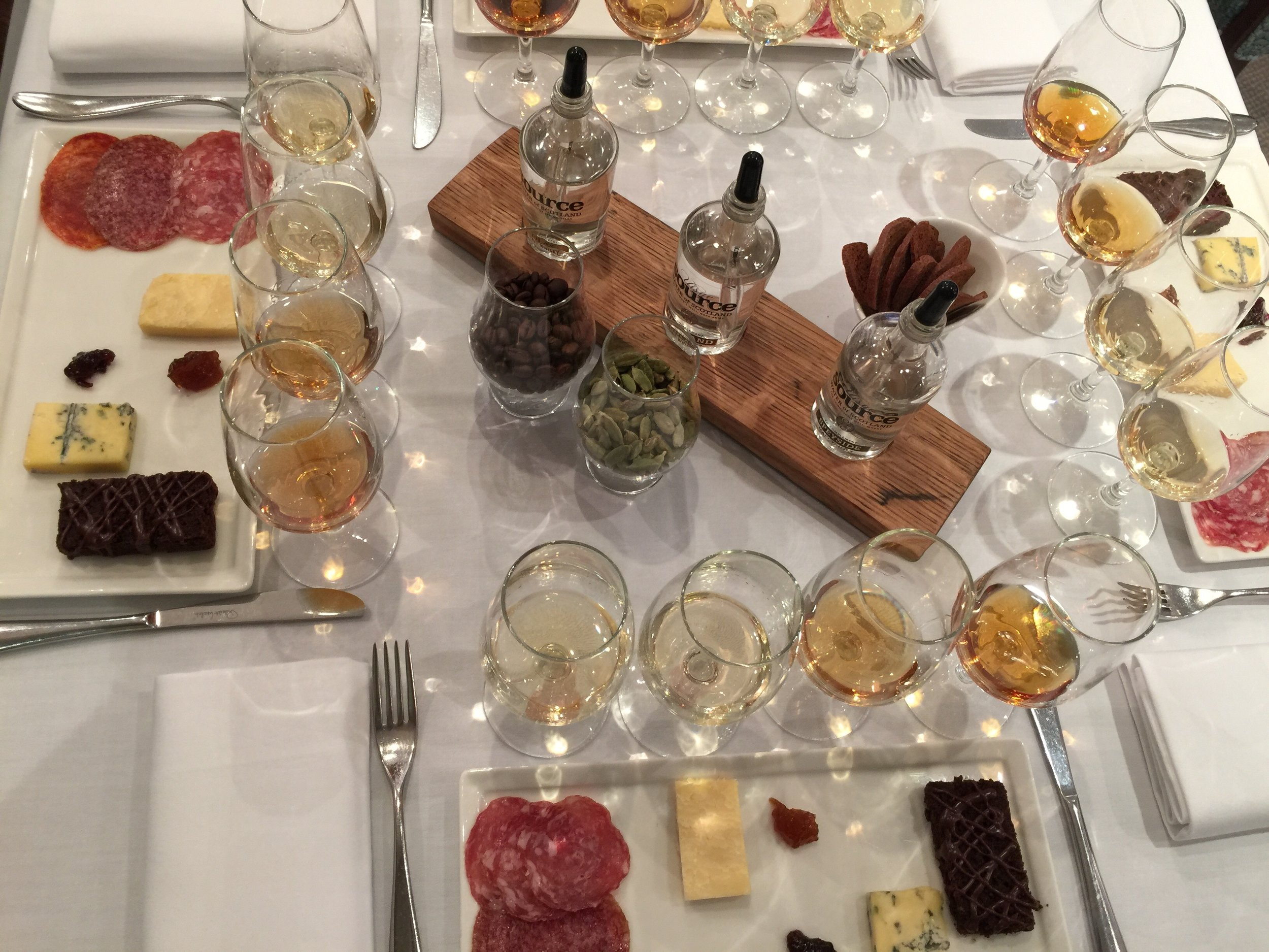 Tables set for the Guild of Food Writers tasting: whiskies, salami, cheeses and complementary chutneys and chocolate cake, plus waters from various whisky regions, and cardamoms and coffee beans to clear to nose.